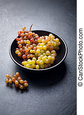 Fresh grape in bowl on a black stone background.