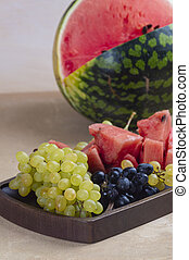 Fresh green and blue grapes, with pieces of watermelon