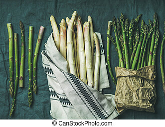 Fresh green and white asparagus in towel, grey background