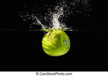 Fresh green apple falling into the water with a splash on a black background closeup