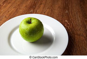 fresh green apple on a white plate