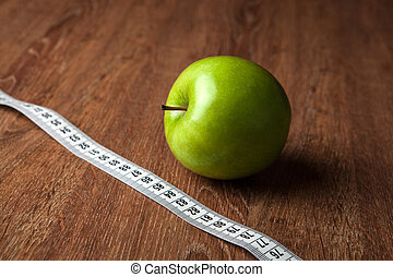 fresh green apple on a wooden table with measure