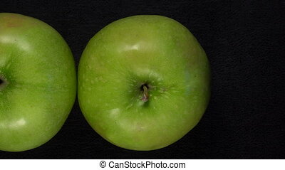 Fresh green apples on black background