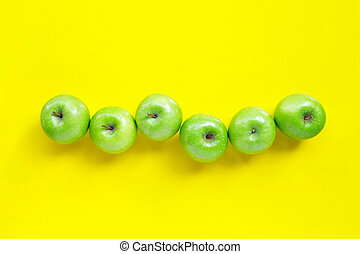 Fresh green apples on yellow background. Top view