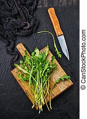 arugula - Fresh green arugula on wooden board. Arugula...