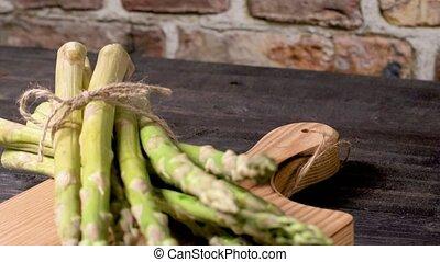 Fresh green asparagus on dark wooden table.