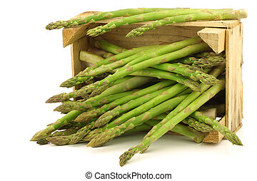 fresh green asparagus shoots in a wooden crate on a white...