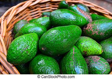 Fresh green Avocados in a basket