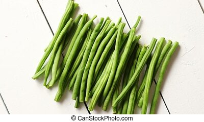 Fresh green bean pods placed on white wooden table. Top...