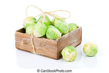 fresh green brussels sprouts in the wooden box, on a white background