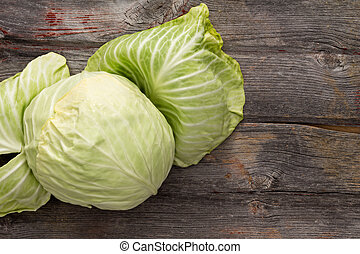Fresh green cabbage with the outer leaves folded back to display the heart on a rustic wooden table with copyspace