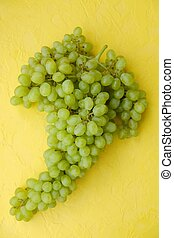 Fresh green grapes on a yellow background