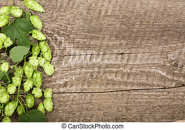 Fresh green hop cones on old wooden background. Ingredient for beer production. Top view with copy space for your text
