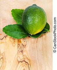 fresh green kaffir lime fruit with leaves on board