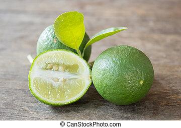 Fresh Green Lemon On Wood Background