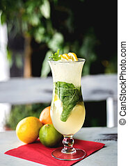 fresh green lime soft lemonade in a glass on wooden table with decorations. Selective focus