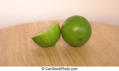 Fresh green limes rotating on wooden table