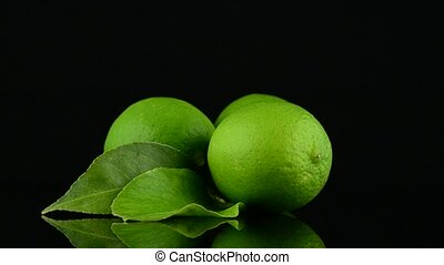 Fresh green limes rotating on black reflective background.