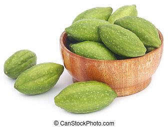 Fresh green medicinal haritaki fruits over white background
