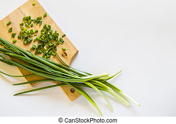 Fresh green onion feathers and cut into pieces on a wooden chopping Board. Top view, flat lay, copying space isolated on white background