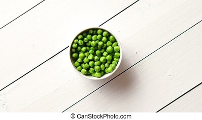 Fresh green pea seeds in a white ceramic bowl. Shot from ...
