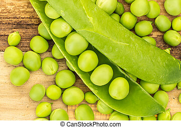 Fresh green peas closeup on wooden surface