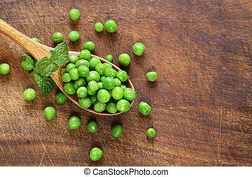 Fresh green peas in a wooden spoon