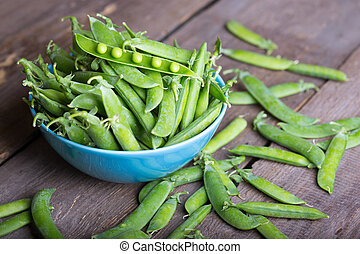 green pea - Fresh green peas on a wooden table