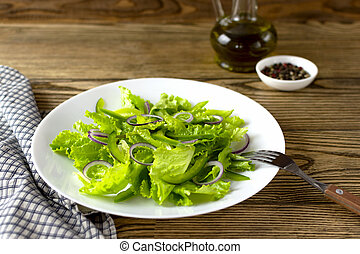 Fresh Green salad in white plate on dark rustic background. Selected focus.