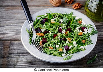 Fresh green salad with arugula, beets, walnuts and feta cheese