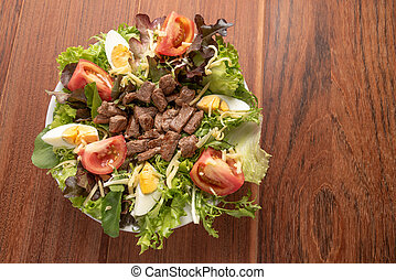 Fresh green salad with arugula, romaine, tomato, eggs, steak mignon and lettuce in a bowl on a wooden background