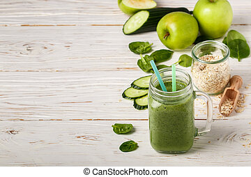 Fresh green smoothie from fruit and vegetables for a healthy lifestyle and ingredients for making dietary drink (spinach, green Apple, cucumber, oatmeal). Detox. Copy space. Selective focus