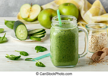 Fresh green smoothie from fruit and vegetables for a healthy lifestyle and ingredients for making dietary drink (spinach, green Apple, cucumber, oatmeal). Selective focus