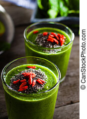 Fresh green smoothie sprinkled with chia seeds and goji berries in the background fruits and vegetables on wooden table.