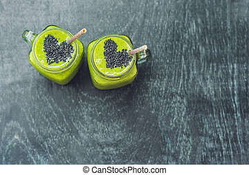 Fresh green smoothie with banana and spinach with heart of sesame seeds. Love for a healthy raw food concept