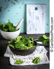 fresh green spinach leaves in a black round cast-iron frying pan