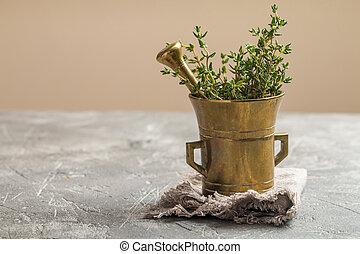 Fresh green thyme in old metal mortar