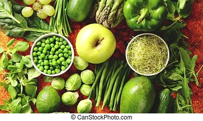 Fresh green vegetables and fruits assortment placed on a...