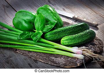 Fresh green vegetables on wooden background