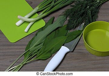 Fresh greens neatly laid out on the tabletop. Fragrant onions, dill and wild garlic. Near the container for salad, chopping board and kitchen knife.
