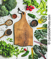Fresh raw greens, unprocessed vegetables and grains over light grey marble kitchen countertop, wooden board in center, top view, copy space. Healthy, clean eating, vegan, detox, dieting food concept