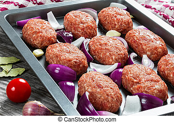 fresh ground raw meat cutlets in baking dish