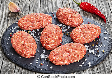 fresh ground raw meat cutlets on slate plate