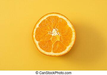 Fresh half orange on yellow background