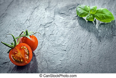 Fresh halved tomato and fresh basil arranged in the the ...