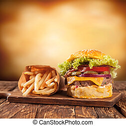 Fresh hamburger with fries served on wood