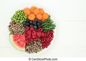 Fresh health food with quinoa salad, sprouting seeds, edamame beans, carrots, samphire, berry fruit and melon. Super food high in antioxidants, anthocyanins, protein, vitamin and dietary fibre.