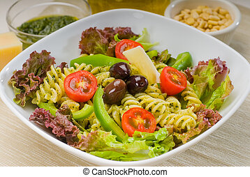 fresh healthy homemade italian fusilli pasta salad with parmesan cheese, pachino cherry tomatoes, black olives and mix vegetables ,dressed with extra-virgin olive oil and pesto sauce
