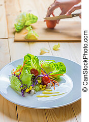 Fresh healthy salad on wooden table.