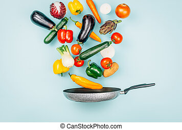 Fresh healthy vegetables falling in a pan